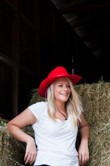 Girl leaning on hay bales in barn