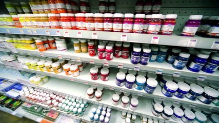 Many cans of paint are on shelves in store