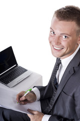 Happy young businessman using laptop in business