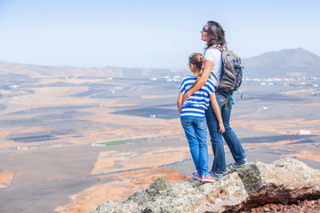 Mother and daughter standing on cliff's edge