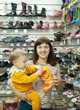 woman with child chooses baby boots