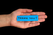 Frase Thank You on paper and hand