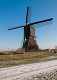 Dutch windmill with scoopwheel pump and a snowy road