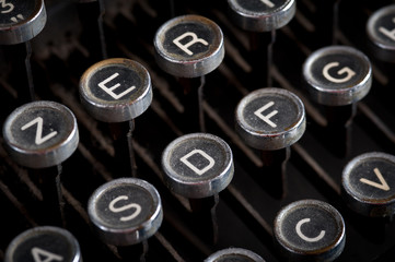Old typewriter keyboard with silver and black round keys backgro