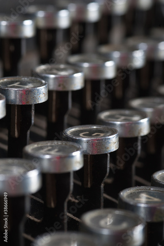 Old typewriter keyboard with silver and black round keys.