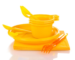 Bright yellow plastic tableware and napkins isolated on white