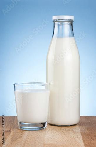 Leinwandbild Motiv Bottle of fresh milk and glass is wooden table on a blue backgro