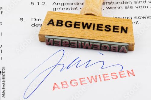 Holzstempel auf Dokument: Abgewiesen