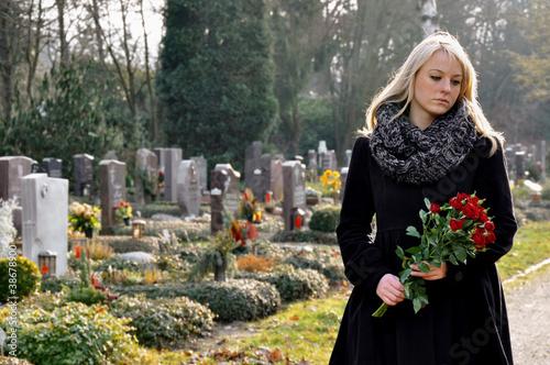 Fotobehang Begraafplaats Junge Frau trauert auf Friedhof