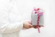 Schönes Geschenk mit Schleife wird von Frau gehalten