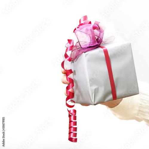 Ein Geschenk mit Schleife wird gehalten