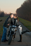 Attractive young couple kissing over the motorcycle