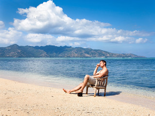 Young man in chair resting on the beach