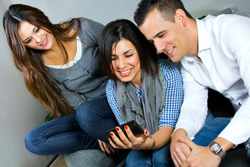 three friends having fun with a mobile phone