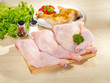 Fresh raw and roasted chicken legs arrangement on cutting board