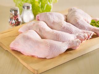 Fresh raw chicken legs arrangement on kitchen board