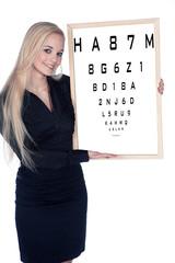 Junge Optikerin  hält Sehtest Tafel freundlich hoch