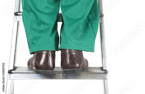 Feet of worker on steel ladder