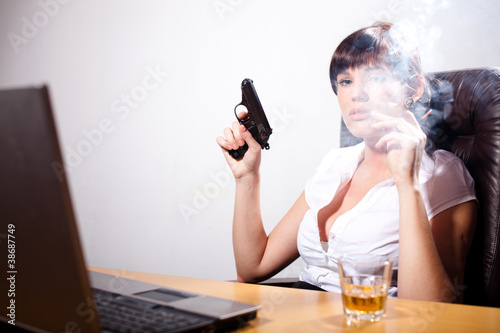 Young businesswoman smoking a cigar, with a gun in her hand