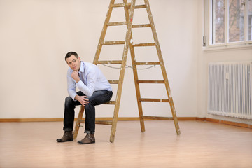 Moving to new office or house: man sitting on ladder