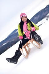 Young woman in snow with sledge