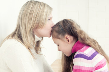 Young caucasian woman kissing her little daughter