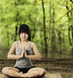 Asian Woman Meditating in Forest