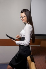 smiling business woman with calculator and glasses in the office