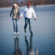 Couple ice skating outdoors on a pond on a lovely winter day
