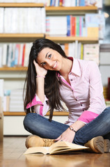 smiling female college student sitting on floor in library, read