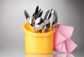 Kitchen cutlery, knives, forks and spoons in yellow stand with