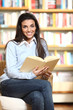 smiling female student with book in hands sitting in a chair in