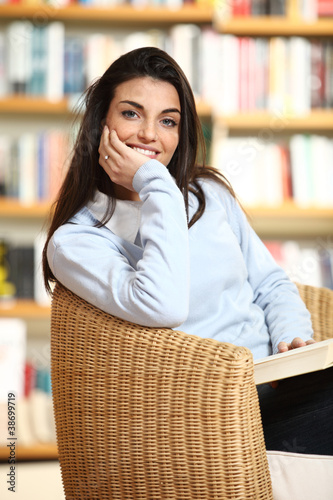 smiling female student with book in hands looking at camera. On