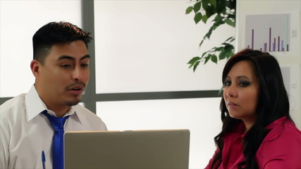 Attractive Hispanic coworkers look up at camera and smile.