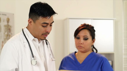 A Hispanic doctor and his nurse discuss file with woman