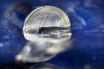 1 Euro Muenze versinkt inm Wasser