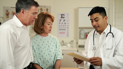 Hispanic Doctor Talks to Couple