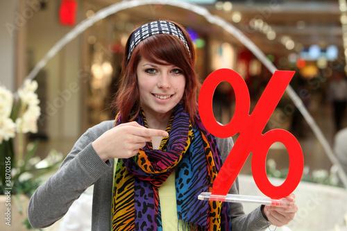 Leinwanddruck Bild Junge Frau mit Prozentzeichen im Schlussverkauf