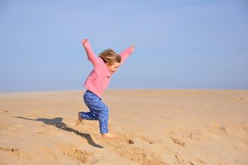Fillette sautant d'une dune