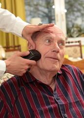 Pflegebeduertiger alter Mann mit Pflegerin