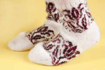 Children's feet in wool socks on a yellow background