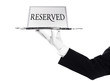 Reserved -A hand holding silver tray with reserved sign
