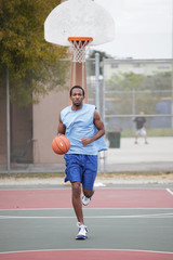 Basketball player running and dribbling the ball