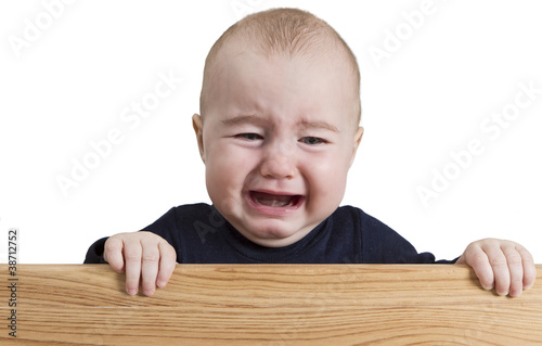 crying young child holding wooden board
