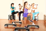 people at the gym exercising with dumbbells