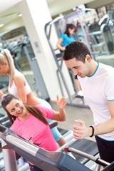 personal trainer encouraging man using treadmill