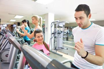 trainer instructing man on treadmill