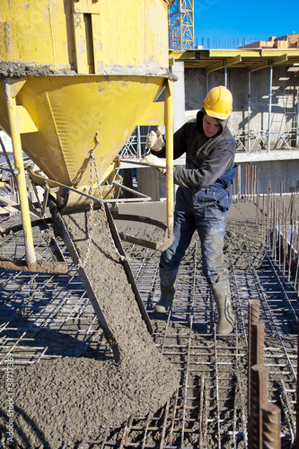 Builder worker pouring concrete at construction site