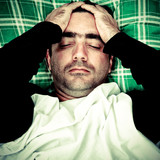 Stressed or mentally disturbed man laying in bed poster