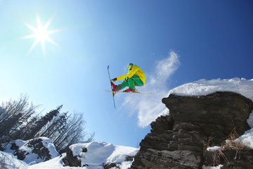 Cool skier jumping against blue sky from the rock